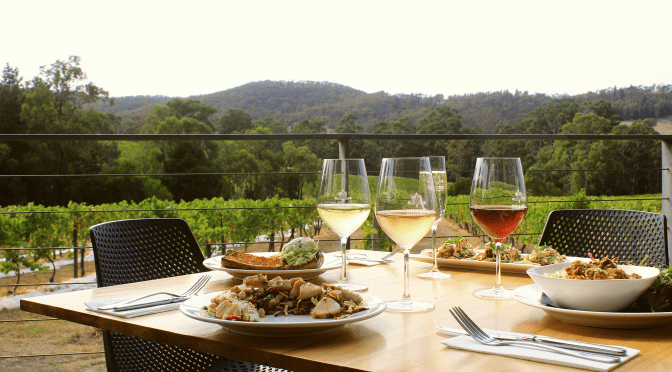 Side view of a Steel's Gate lunch table setting with savoury dishes and wine - set against a backdrop of vineyards and tree covered hills